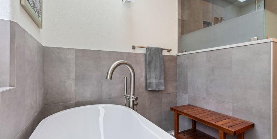 Natural Stone Tile Surrounding White Bathtub.