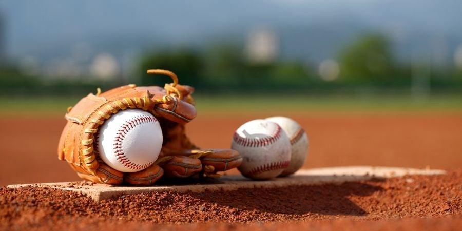 Baseball glove with baseballs resting on baseball diamond